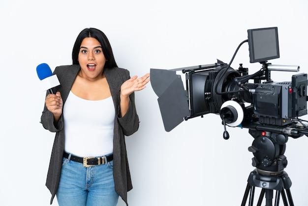 Journaliste femme tenant un microphone et rapportant des nouvelles sur le mur blanc avec une expression faciale choquée