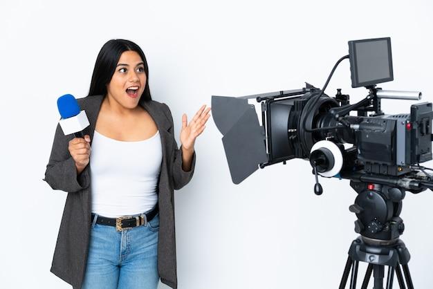 Journaliste femme tenant un microphone et rapportant des nouvelles sur le mur blanc avec une expression faciale surprise