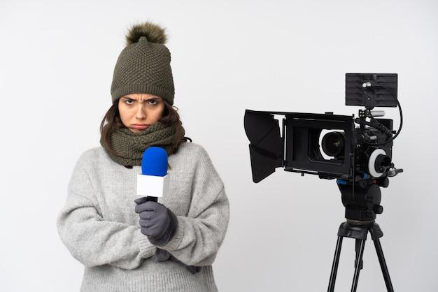 Journaliste femme tenant un microphone et rapportant des nouvelles sur un mur blanc isolé, bouleversé
