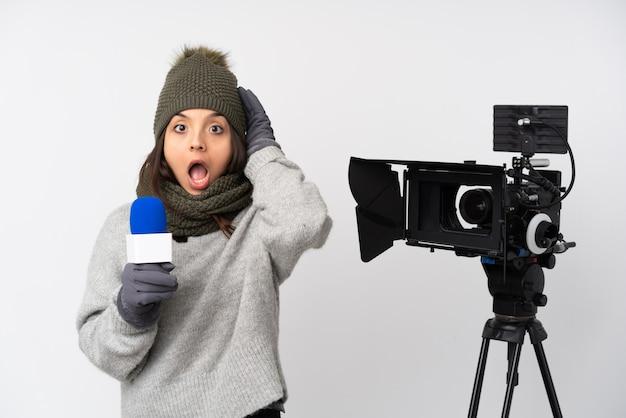 Journaliste femme tenant un microphone et rapportant des nouvelles sur un mur blanc isolé avec expression surprise