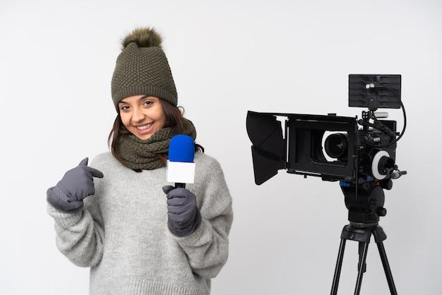 Journaliste femme tenant un microphone et rapportant des nouvelles sur un mur blanc isolé, fier et satisfait de lui-même
