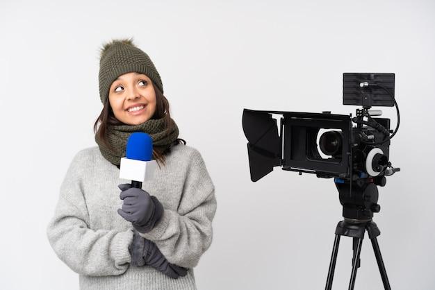 Journaliste femme tenant un microphone et rapportant des nouvelles sur un mur blanc isolé en levant tout en souriant