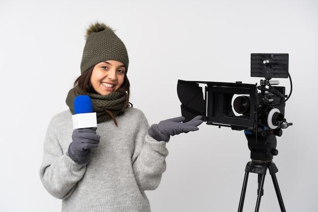 Journaliste femme tenant un microphone et rapportant des nouvelles sur un mur blanc isolé tenant copyspace imaginaire sur la paume pour insérer une annonce