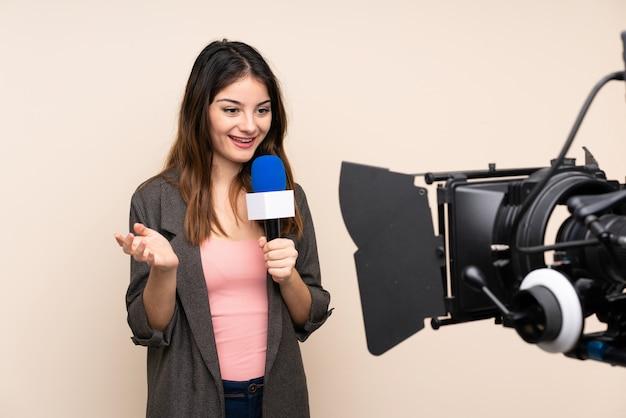 Journaliste femme tenant un microphone et rapportant des nouvelles sur un mur blanc isolé