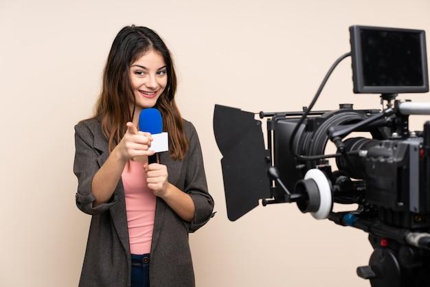 Journaliste femme tenant un microphone et rapportant des nouvelles sur le mur blanc