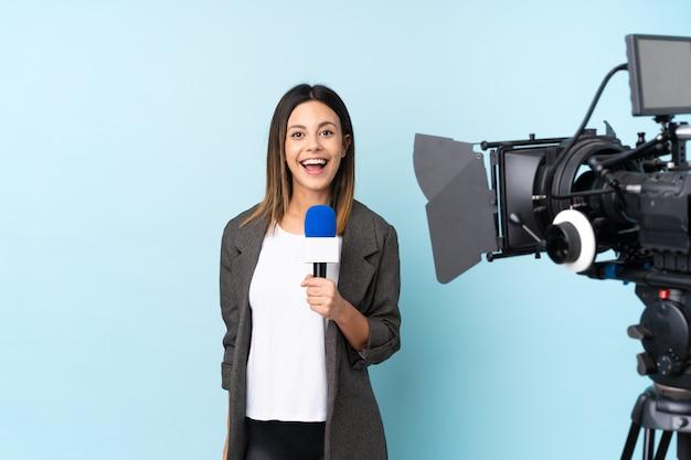 Journaliste femme tenant un microphone et rapportant des nouvelles sur le mur bleu avec une expression faciale surprise