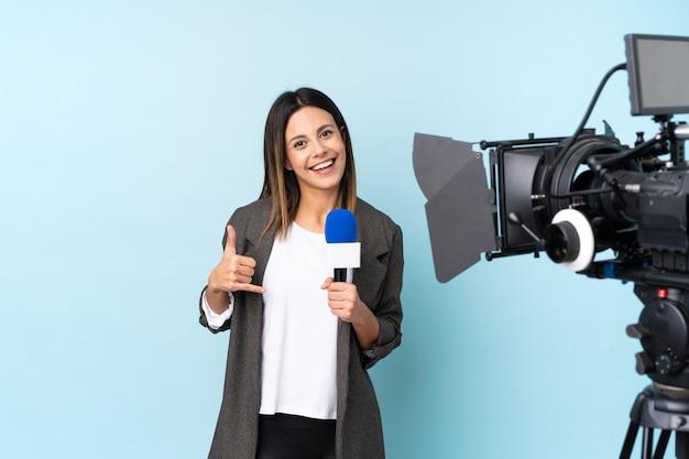 Journaliste femme tenant un microphone et rapportant des nouvelles sur le mur bleu faisant un geste de téléphone
