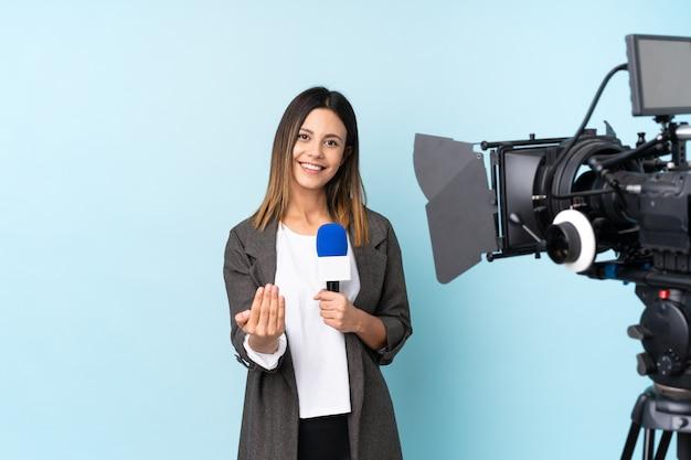 Journaliste femme tenant un microphone et rapportant des nouvelles sur le mur bleu invitant à venir