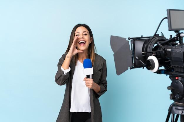 Journaliste femme tenant un microphone et rapportant des nouvelles sur le mur bleu isolé criant avec la bouche grande ouverte