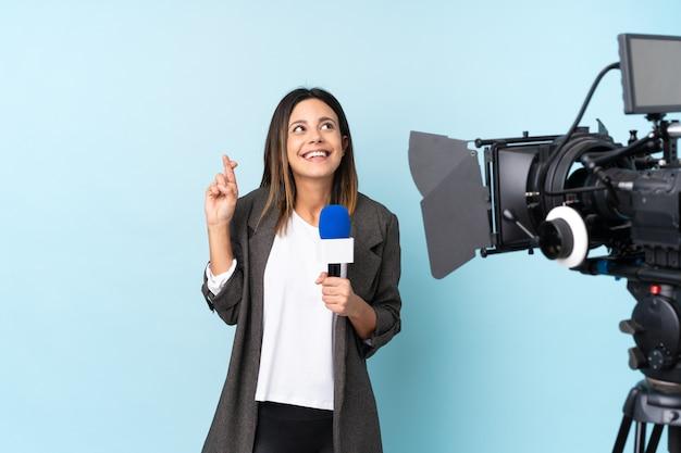 Journaliste femme tenant un microphone et rapportant des nouvelles sur le mur bleu isolé avec les doigts traversant