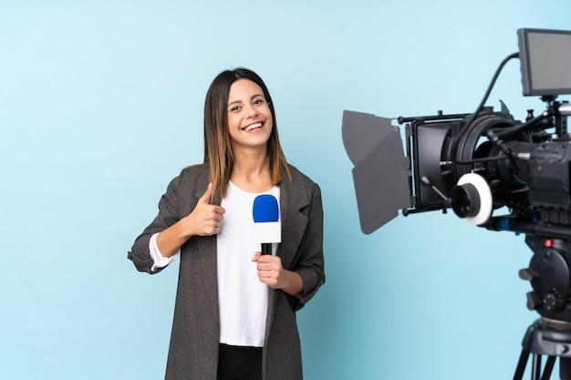 Journaliste femme tenant un microphone et rapportant des nouvelles sur le mur bleu isolé donnant un geste du pouce levé