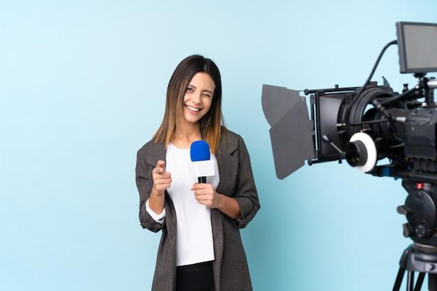 Journaliste femme tenant un microphone et rapportant des nouvelles sur le mur bleu isolé pointe du doigt