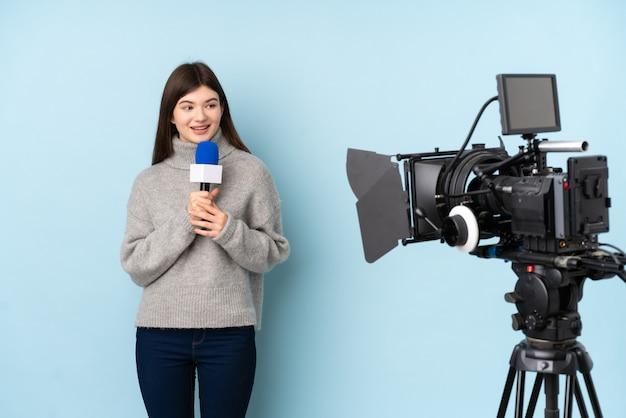 Journaliste femme tenant un microphone et rapportant des nouvelles sur le mur bleu isolé
