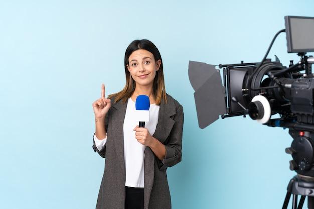 Journaliste femme tenant un microphone et rapportant des nouvelles sur le mur bleu pointant avec l'index une excellente idée