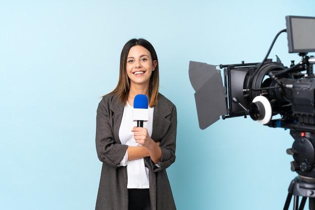 Journaliste femme tenant un microphone et rapportant des nouvelles sur le mur bleu en riant