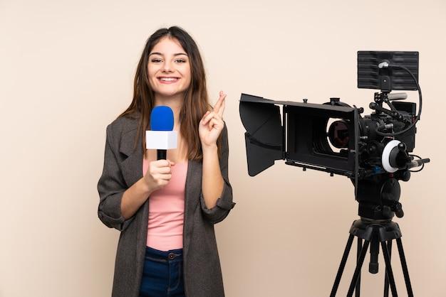 Journaliste femme tenant un microphone et rapportant des nouvelles sur le mur avec les doigts qui se croisent