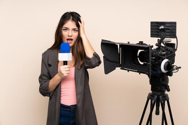 Journaliste femme tenant un microphone et rapportant des nouvelles sur le mur avec une expression faciale surprise
