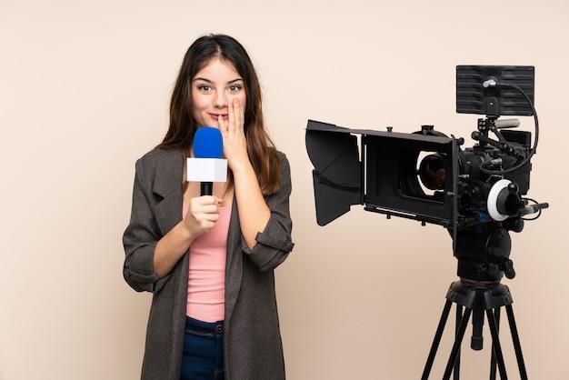 Journaliste femme tenant un microphone et rapportant des nouvelles sur un mur isolé avec une expression faciale surprise