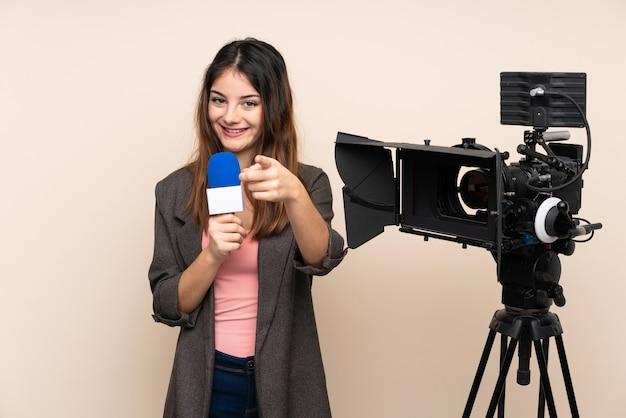 Journaliste femme tenant un microphone et rapportant des nouvelles sur le mur isolé pointe le doigt vers vous