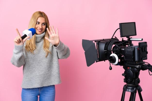 Journaliste femme tenant un microphone et rapportant des nouvelles sur un mur rose comptant sept avec les doigts