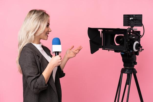 Journaliste femme tenant un microphone et rapportant des nouvelles sur le mur rose