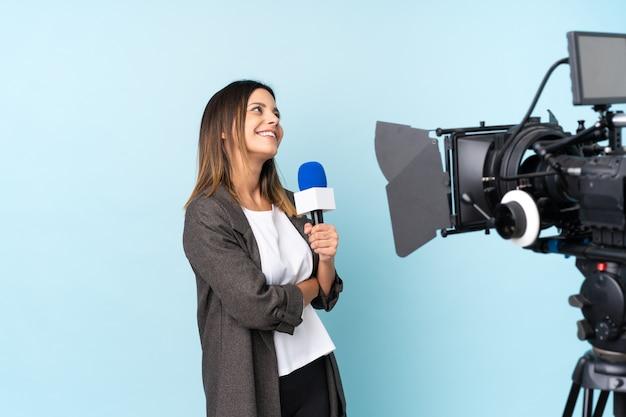 Journaliste femme tenant un microphone et rapportant des nouvelles en riant