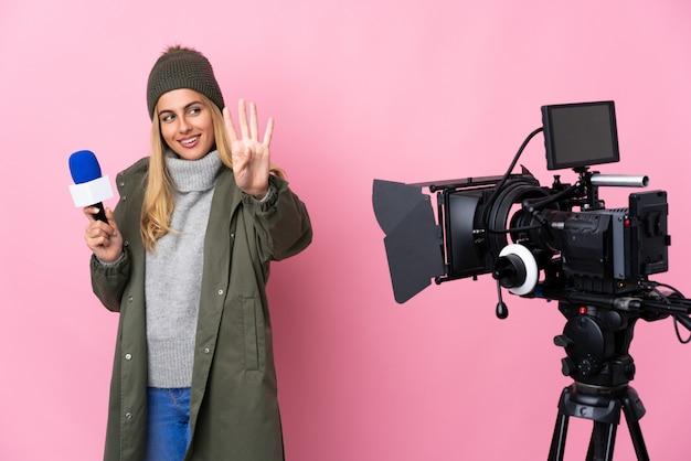 Journaliste femme tenant un microphone et rapportant des nouvelles sur rose isolé heureux et en comptant quatre avec les doigts