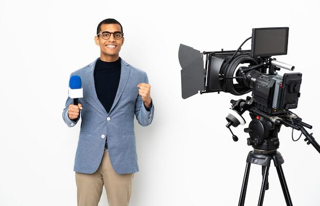 Journaliste homme afro-américain tenant un microphone et rapportant des nouvelles sur un mur blanc isolé célébrant une victoire en position de gagnant