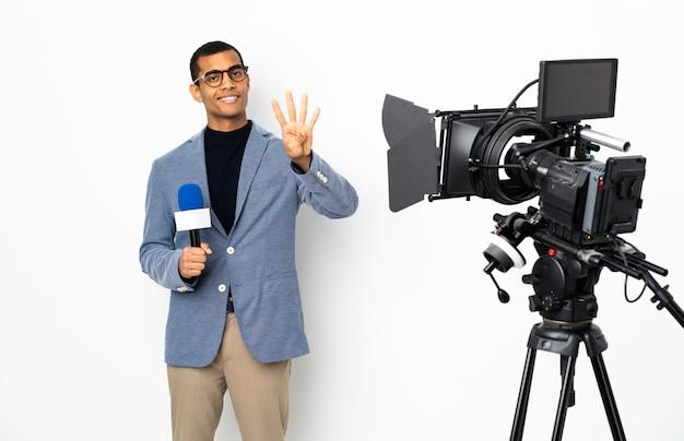 Journaliste homme afro-américain tenant un microphone et rapportant des nouvelles sur un mur blanc isolé heureux et en comptant quatre avec les doigts