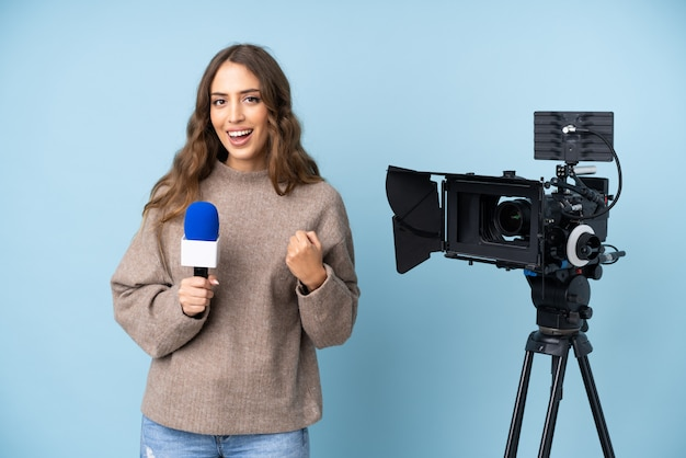 Journaliste jeune femme tenant un microphone et rapportant des nouvelles célébrant une victoire