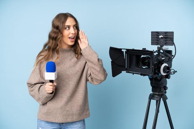 Journaliste jeune femme tenant un microphone et rapportant des nouvelles criant avec la bouche grande ouverte