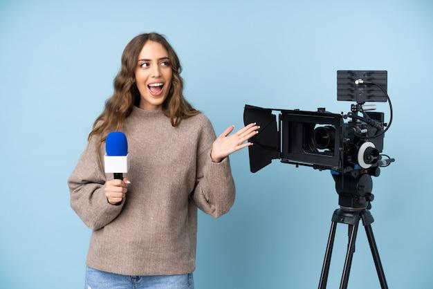 Journaliste jeune femme tenant un microphone et rapportant des nouvelles avec une expression faciale surprise