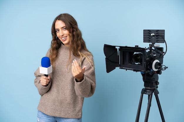 Journaliste jeune femme tenant un microphone et rapportant des nouvelles invitant à venir