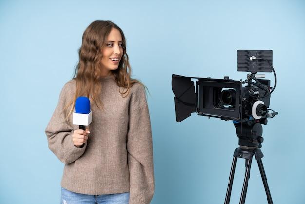 Journaliste jeune femme tenant un microphone et rapportant les nouvelles à la recherche de côté