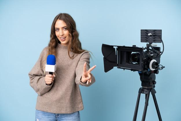 Journaliste jeune femme tenant un microphone et rapportant des nouvelles souriant et montrant le signe de la victoire