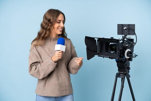 Journaliste jeune femme tenant un microphone et rapportant des nouvelles