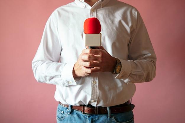 Journaliste avec microphone en main fond rose