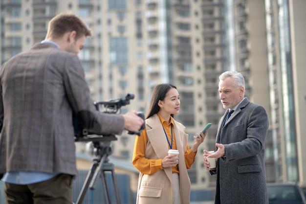 Journaliste portant une tenue beige posant des questions à un homme aux cheveux gris