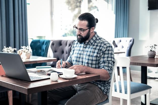 Journaliste professionnel. journaliste professionnel prospère portant des lunettes travaillant dur pour prendre des notes