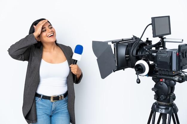 Une journaliste tenant un microphone et rapportant des nouvelles sur le mur blanc a réalisé quelque chose et a voulu la solution