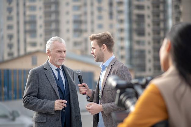Les journalistes de la télévision à la recherche de parler à un homme d'affaires célèbre
