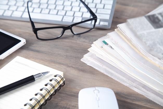 Journaux, clavier d'ordinateur, lunettes sur la table en bois.