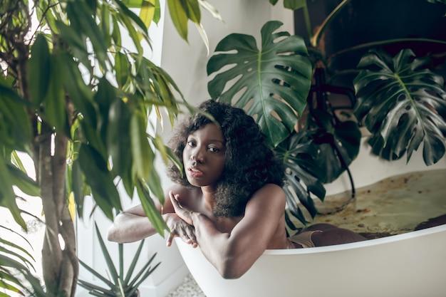 Journée au spa. jolie femme afro-américaine se détendre dans un bain