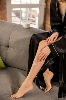 Journée de la beauté. femme portant une robe de soie faisant sa routine quotidienne de soins de la peau à la maison. elle a l'air satisfaite, met de la crème hydratante sur sa peau sur des jambes en forme, souriante. concept de beauté, soins personnels, cosmétiques, jeunesse.