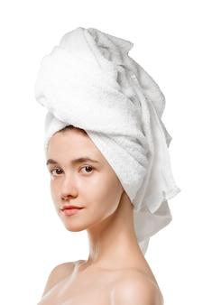 Journée de la beauté. femme portant une serviette faisant sa routine quotidienne de soins de la peau isolée sur fond de studio blanc