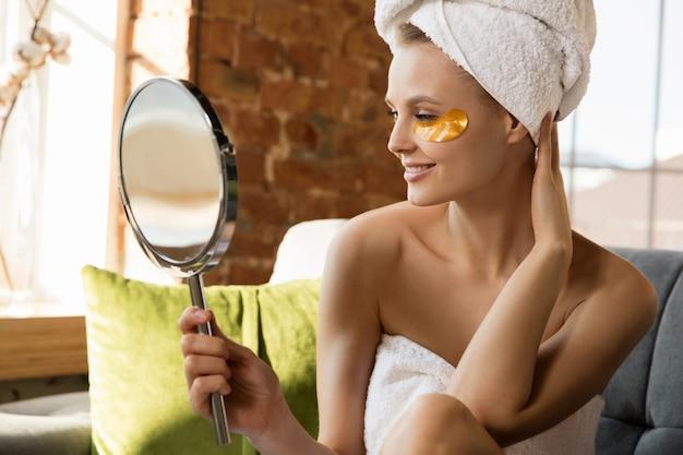 Journée de la beauté. femme portant une serviette faisant sa routine quotidienne de soins de la peau à la maison. mettre des cache-œil dorés, regarder son reflet dans un miroir. concept de beauté, soins personnels, cosmétiques, jeunesse.
