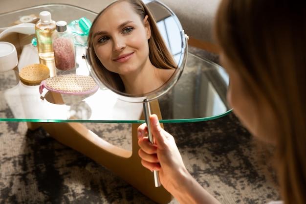 Journée de la beauté. femme portant une serviette faisant sa routine quotidienne de soins de la peau à la maison. mettre de l'hydratant et de la crème, en regardant son reflet dans le miroir. concept de beauté, soins personnels, cosmétiques, jeunesse.