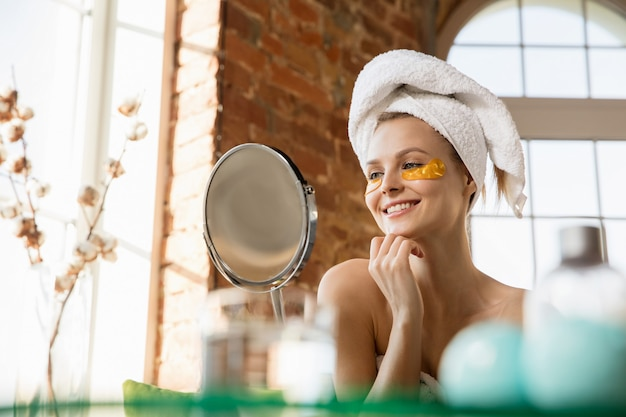 Journée de la beauté femme portant une serviette faisant sa routine quotidienne de soins de la peau à la maison