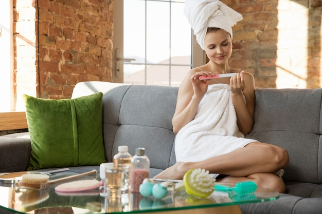 Journée de la beauté. femme portant une serviette faisant sa routine quotidienne de soins de la peau et de manucure à la maison. assis sur un canapé semble heureux et calme. concept de beauté, soins personnels, cosmétiques, jeunesse, week-end à la maison, spa.