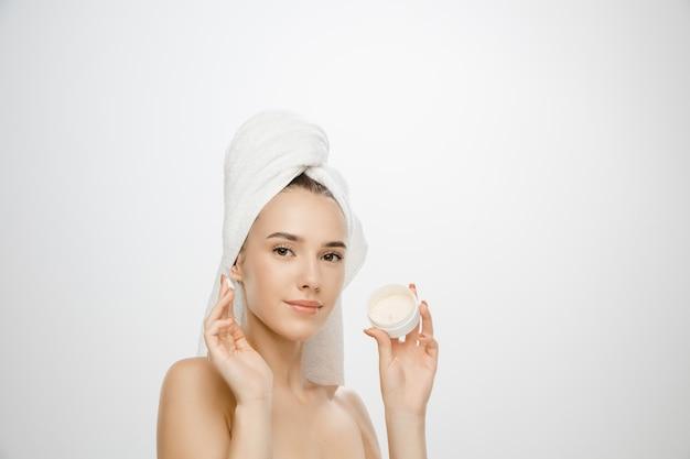 Journée de la beauté. femme portant une serviette sur fond de studio blanc avec de la crème. journée auto-soins, soins de la peau, routine beauté. beau modèle féminin caucasien avec une peau bien entretenue. concept de spa, traitement.